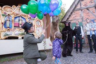 Hist. Jahrmarkt Ballonverkauf mit Kamel-Bär vor hist Orgelspiel